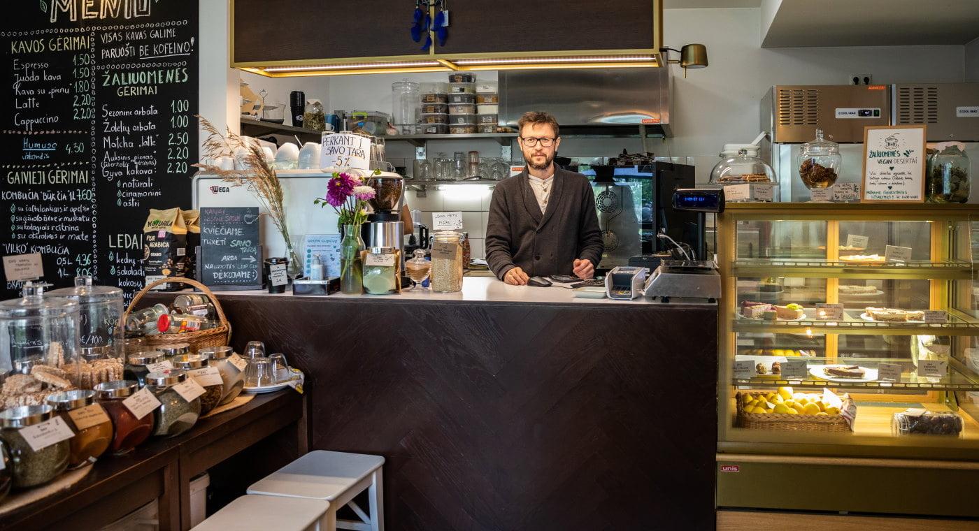 Konstantin standing behind counter in Žaliuomenė