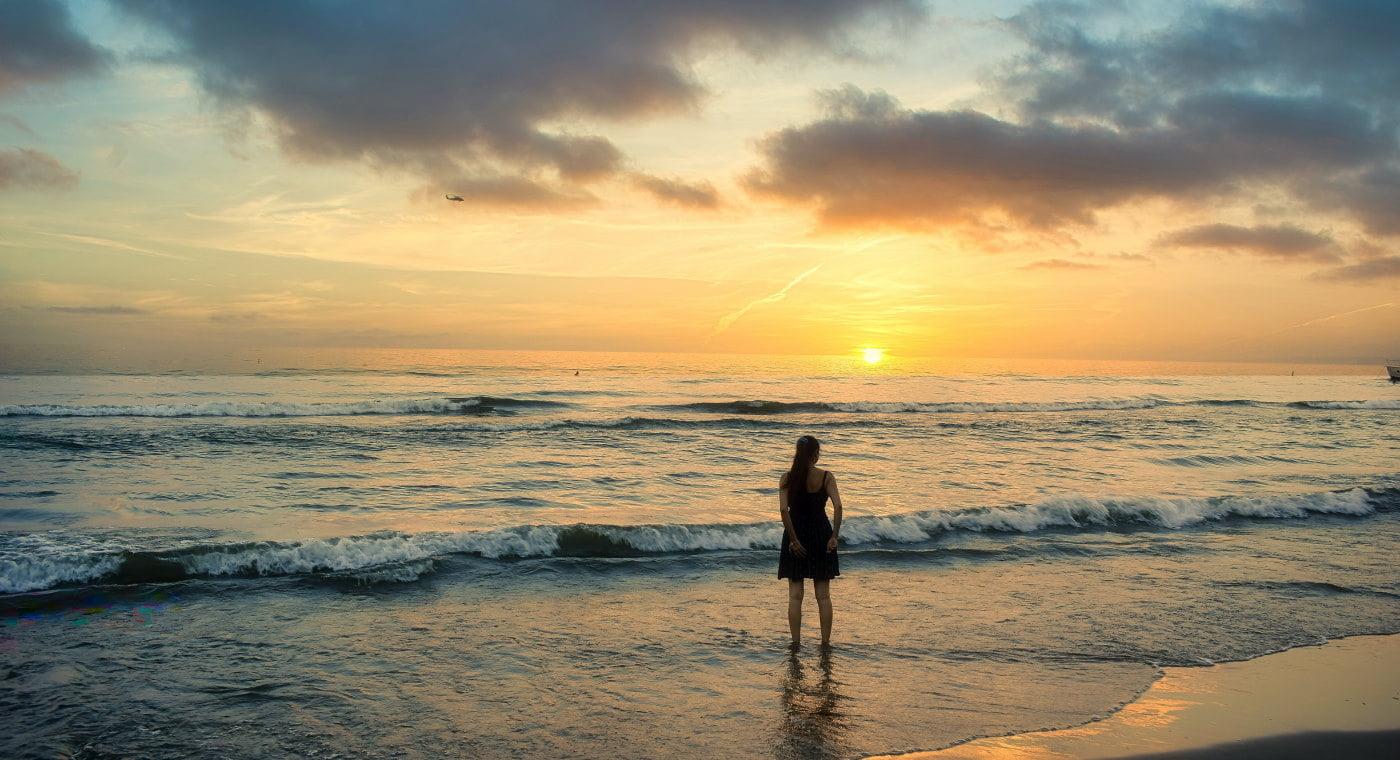 Women on beach watching ocean sunset
